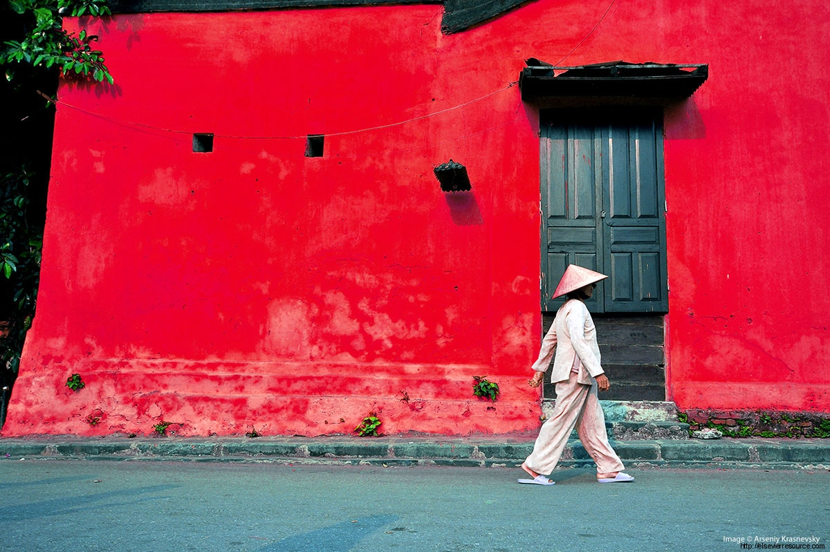 Scene from South-East Asia, woman walking past a building