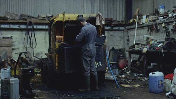 A still from the film 'Landline' showing a young farmer doing maintenance on his Land Rover