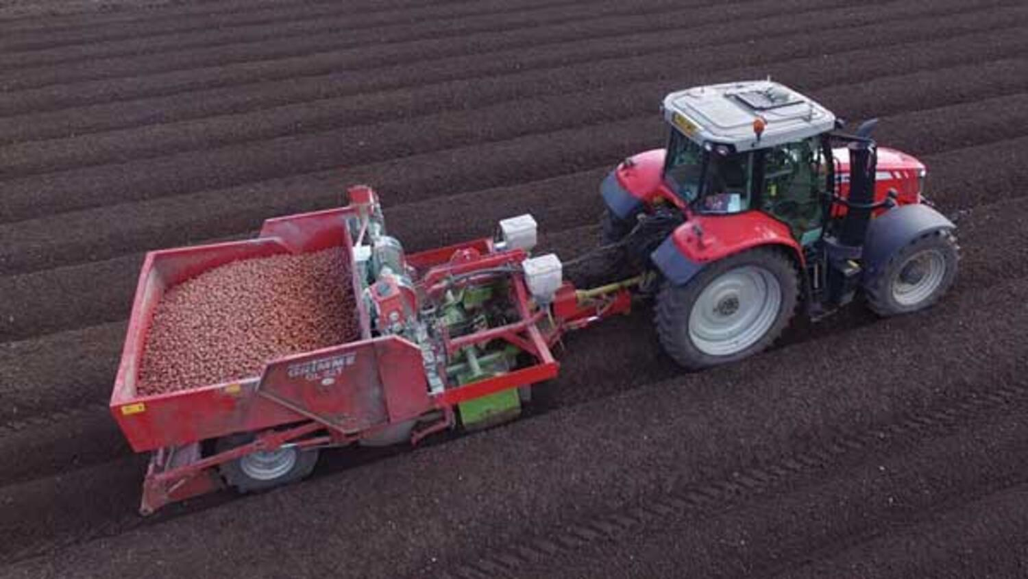 A drone's eye view of a root crop planter, pulled by a tractor as it works in the field